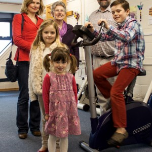 Shows Freddie on the bike, with Mark Boscher (Herts MS Therapy Centre manager) and Freddie's family
