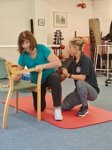 Physiotherapist helping patient to move into a chair